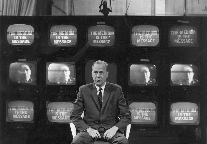 Marshall McLuhan, in front of bank of TV screens