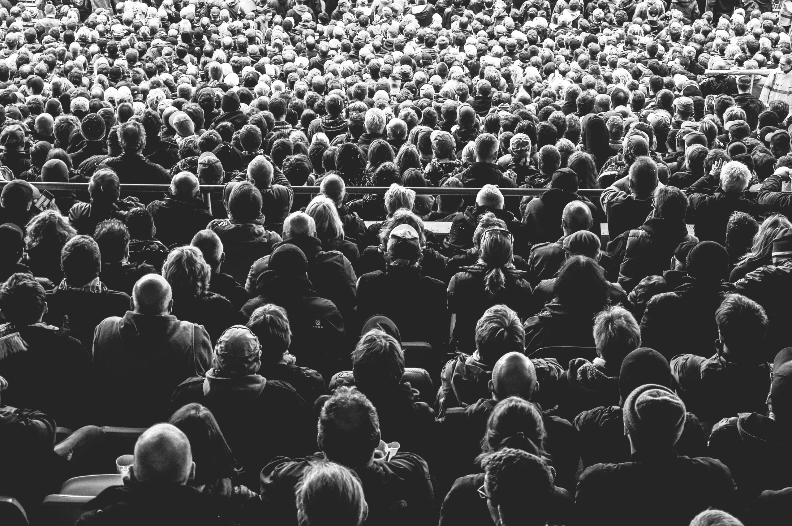 Large audience, from behind, in black and white