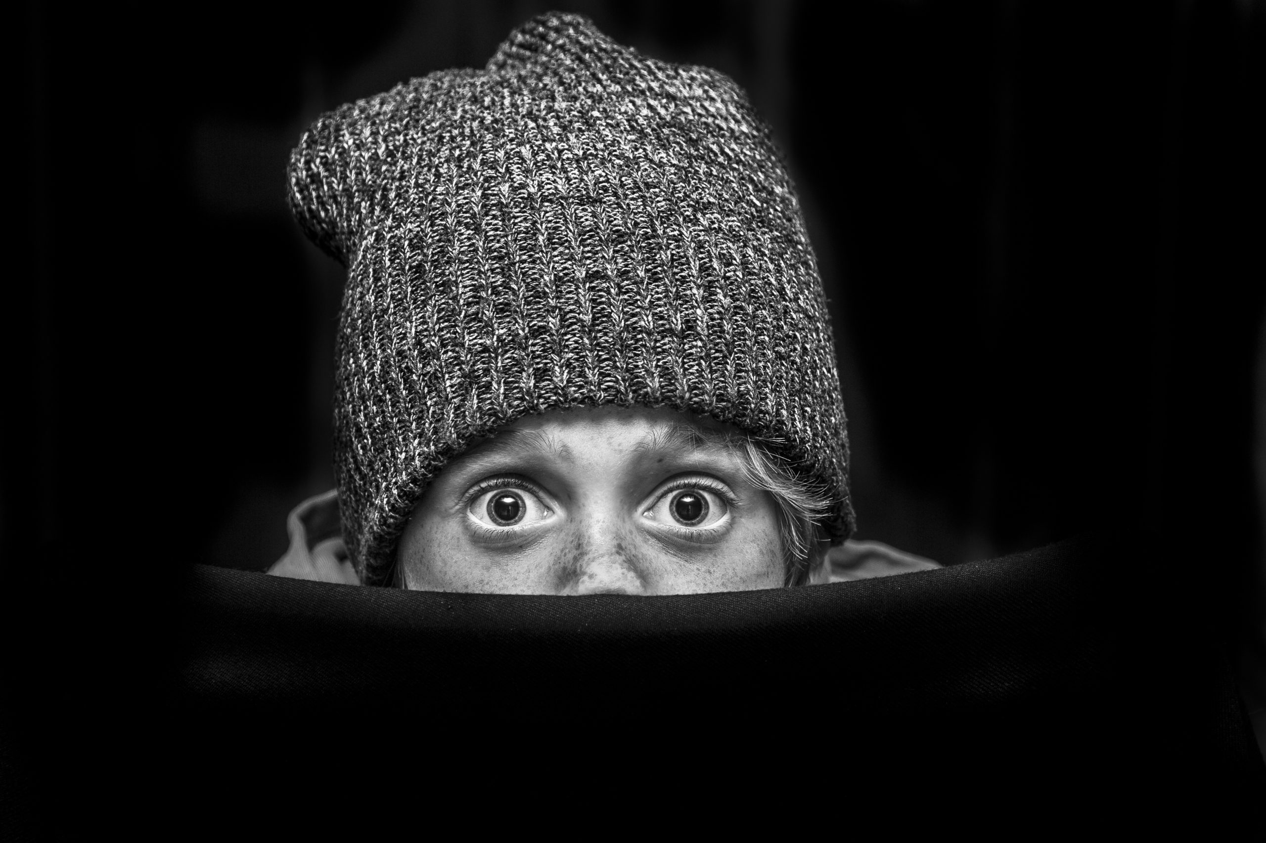 Child peaking out under beanie hat, looking shocked
