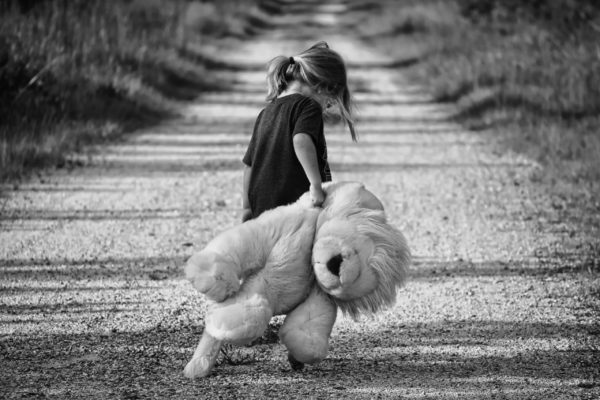 Small girl dragging teddy bear